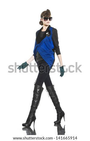image of young fashion model in sunglasses with gloves walking in studio