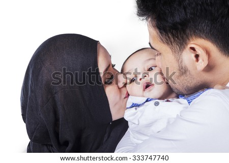 Image of young father and mother holding their son and kissing his cheeks, isolated on white - stock photo