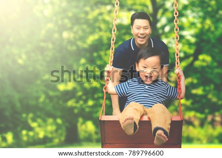 image young father pushing his son の写真素材 今すぐ編集