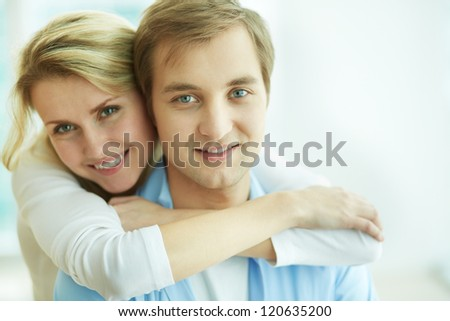 Image of young female embracing her husband and both looking at camera