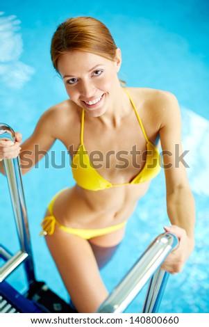 Image of young female in bikini smiling at camera in swimming pool - stock photo