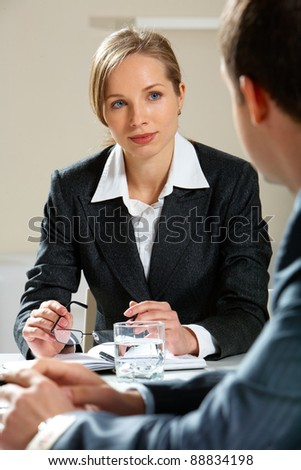 Image of young female looking at her partner while listening to him at meeting - stock photo