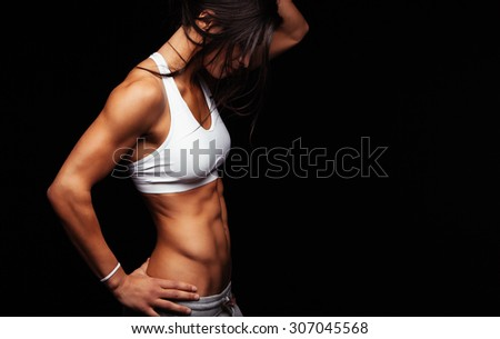 Image of young female model in sportswear standing on black background with copyspace. Woman with muscular torso standing with hand on hips. - stock photo