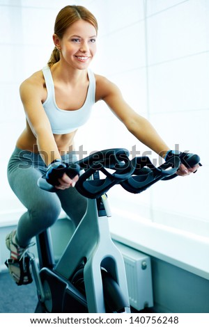 Image of young female training on simulator in gym - stock photo