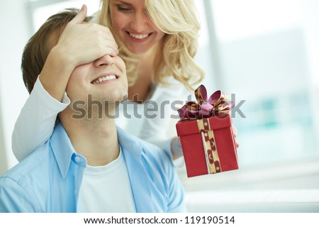 Image of young female with giftbox closing her boyfriend eyes to make a surprise for him - stock photo