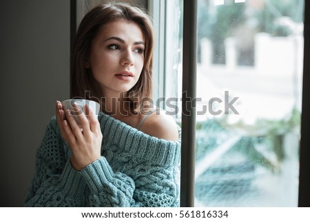 Image of young gorgeous woman look at window in cafe and drinking coffee.