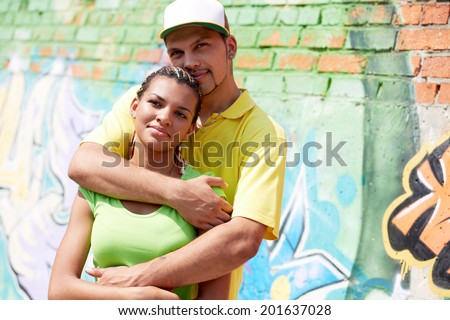 Image of young guy embracing his girlfriend on background of graffiti wall - stock photo