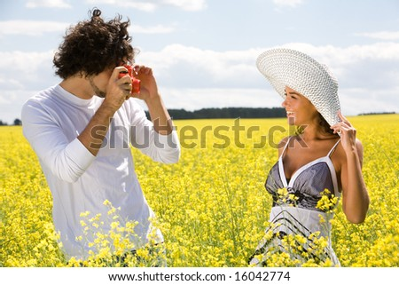 Image of young guy taking photos of pretty girl on yellow field at summer - stock photo