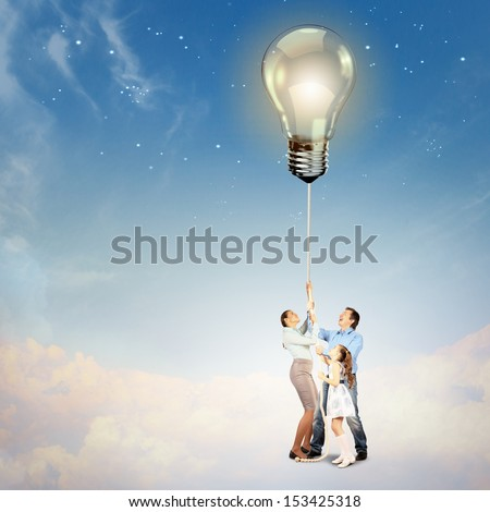Image of young happy family pulling rope with an electric bulb. Idea concept - stock photo