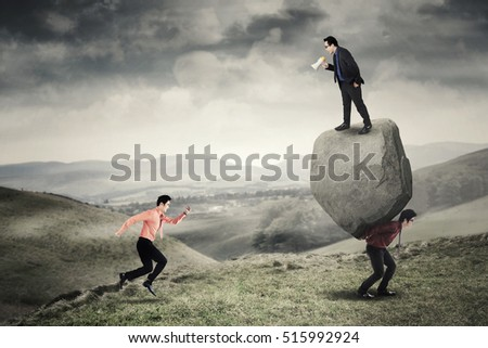 Image of young leader standing on a stone carried by his employee while shouting at a businessman with megaphone to run fast in the hill