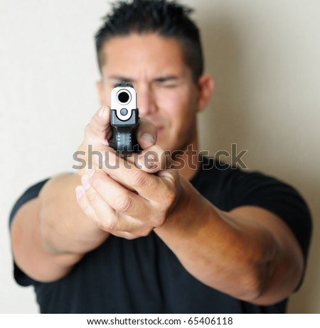 Image of young male pointing gun.  Focus on barrel of gun.