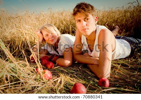 Image of young man and woman on wheat field - stock photo
