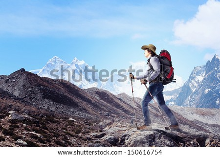 Image of young man mountaineer standing atop of rock