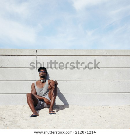Image of young man relaxing on the beach. African male model leaning on a wall. Guy wearing cap and sunglasses resting on beach.  - stock photo