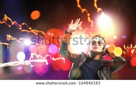 Image of young man rock musician in lights