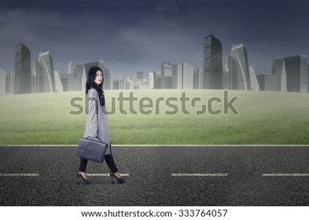 Image of young pretty businesswoman walking on the street while carrying suitcase