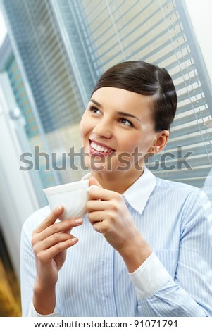 Image of young pretty secretary holding cup of coffee - stock photo