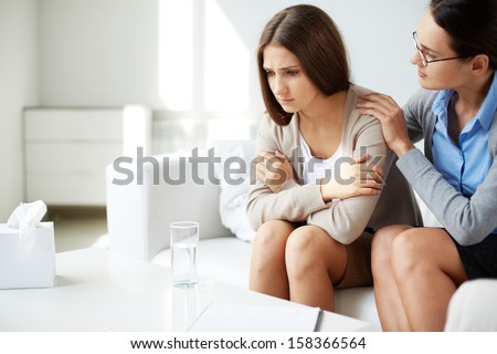 Image of young psychiatrist comforting her sad patient - stock photo