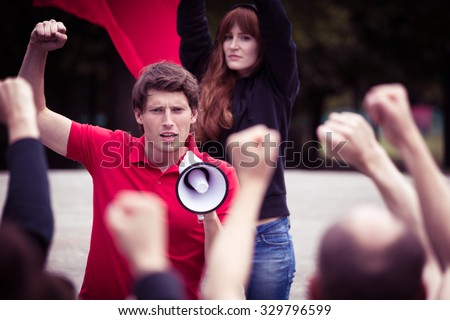 Image of young rebellious man with megaphone during street protest