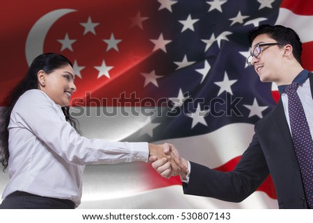 Image of young Singaporean businesswoman shaking hands with American businessman in front of Singaporean and American flags