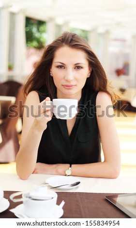 Image of young woman drinks coffee in cafe