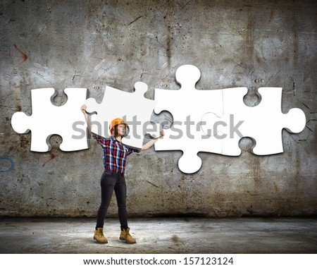 Image of young woman engineer connecting puzzle elements