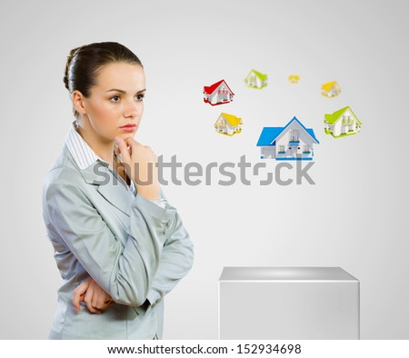 Image of young woman in suit looking at house model. Construction - stock photo
