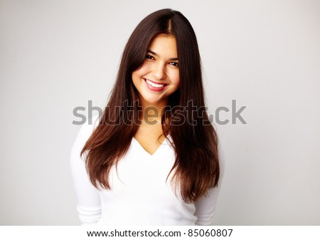 Image of young woman in white pullover smiling at camera