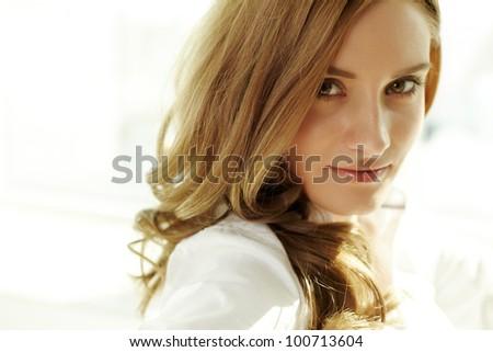 Image of young woman looking at camera - stock photo