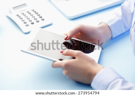 Image of young woman sitting at desk and holding digital tablet while touching the screen. - stock photo