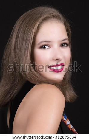 Image of young woman smiling at camera on black background