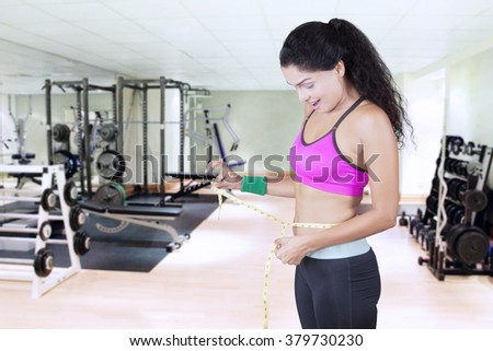Image of young woman standing in the fitness center and measures her waist with a measuring tape - stock photo
