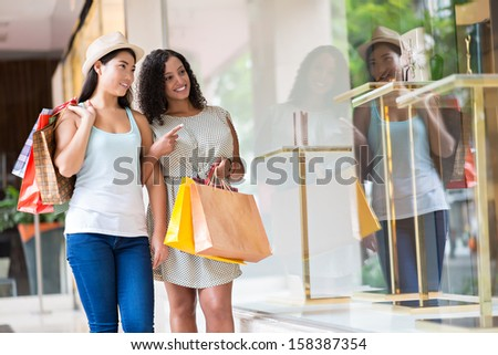 Image of young woman walking in the shopping mall while one of them pointing at something in the shopping-window on the foreground - stock photo