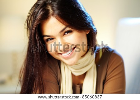 Image of young woman with dark hair smiling at camera - stock photo