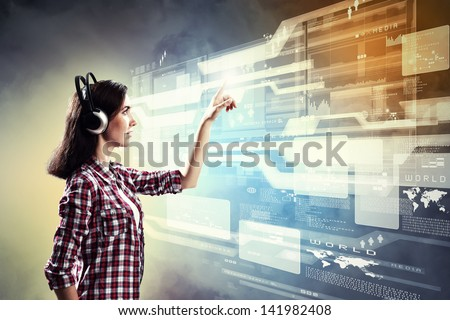 Image of young woman with headphones touching virtual screen - stock photo
