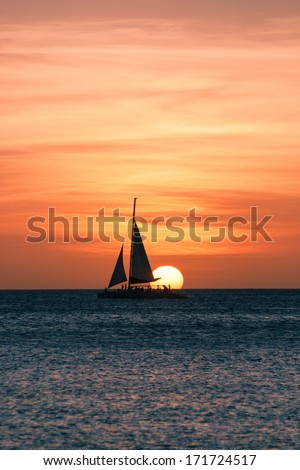 Image showing a sailboat on sea navigating towards the sunset. The image was taken from Palm Beach, Aruba, in the Caribbean Sea.