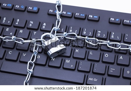 Image shows a keyboard with chain and lock - stock photo