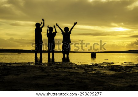 image silhouette boys rise their hand and ball on the ring during sunset sunrise, reflection on water