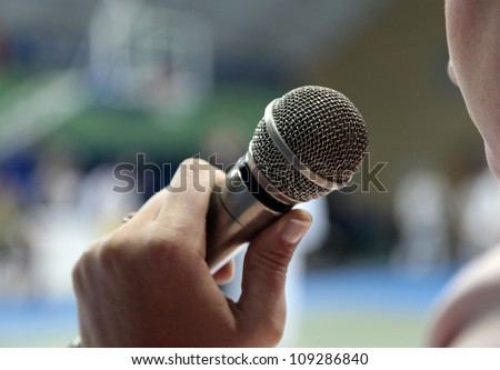 Image the announcer speaks into a microphone. - stock photo