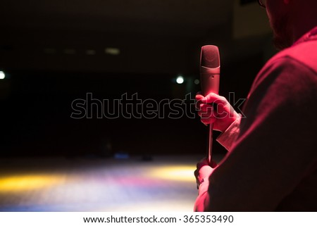 Image the announcer speaks into a microphone. Close up of microphone in concert hall or conference room - stock photo
