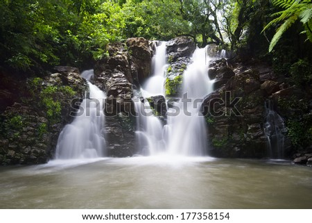 Image using slow shutter speed to capture the motion of Bouma Falls in Fiji and its beautiful surrounding pool of fresh water. - stock photo