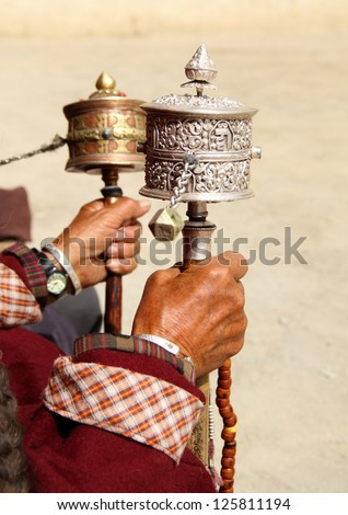 Image with beautiful rotation buddhist prayer wheel at old man's hand in Leh, Ladakh, Jammu & Kashmir, India - stock photo
