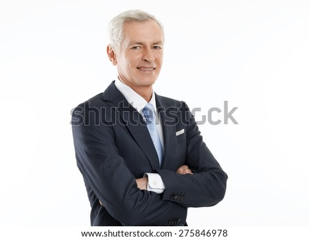 Imagine of executive broker standing against white background while looking at camera and arms crossed.