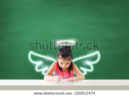 Imagine of little angel.Asian little girl is sitting at the table with her dream - stock photo