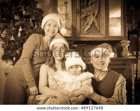 Imitation of  aged photo of happy  family of three generations posing for  Christmas portrait at home
