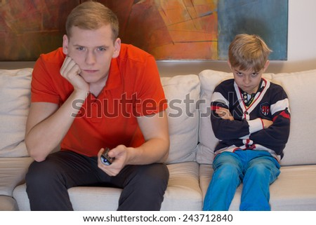 Immature dad watching tv and his bored son - stock photo