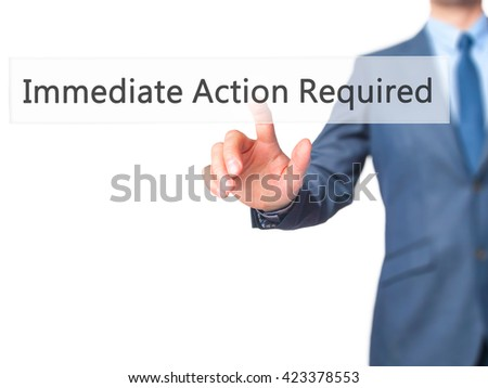 Immediate Action Required - Businessman hand pressing button on touch screen interface. Business, technology, internet concept. Stock Photo