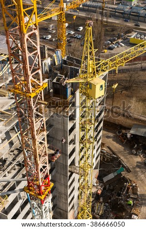 Immense tall tower cranes next to concrete high rise apartment buildings under construction in urban area - stock photo