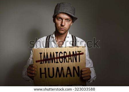 Immigrant holding protest cardboard - stock photo
