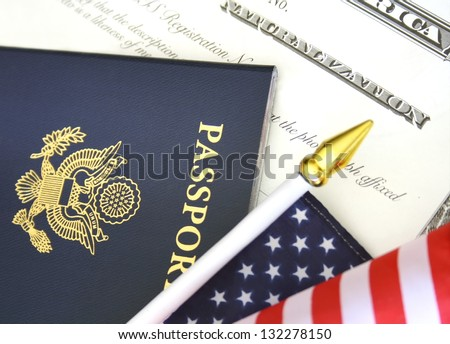 Immigration concept, US passport and flag over a citizenship and naturalization certificate - stock photo